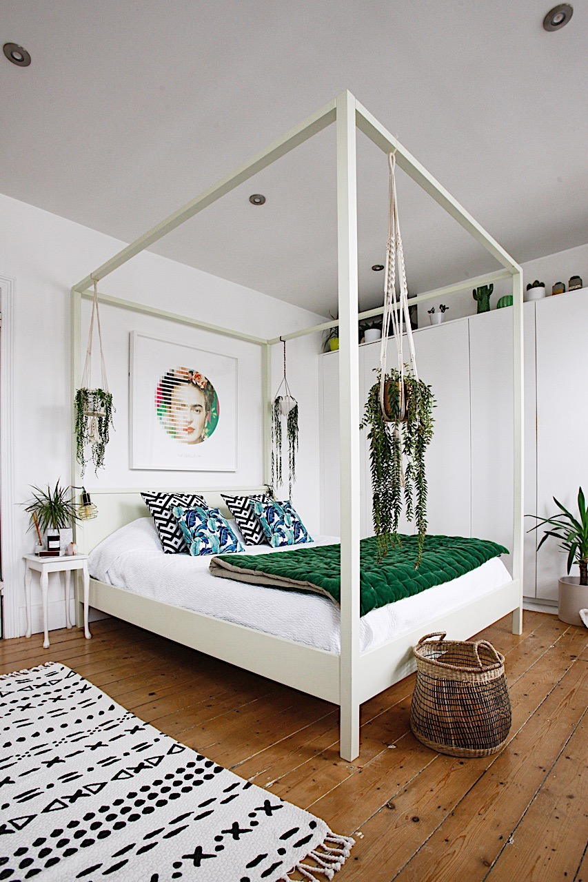 Botanical bedroom with white and green decor and canopy bed