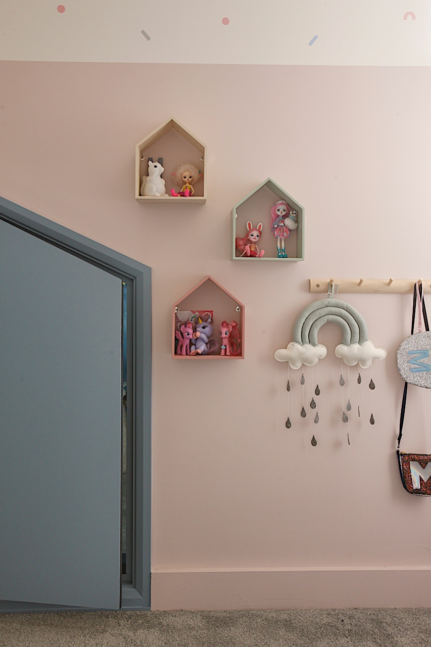 Pastel girls bedroom with cute house shelves and concealed nook